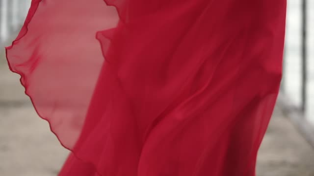 close up shot of the hem of the dress that moves under the gusts of the wind close up shot of the scarlet hem of the dress that flutters under the gusts of the wind, the woman who stands outside is dressed in red shoes on her feet dress stock videos & royalty-free footage