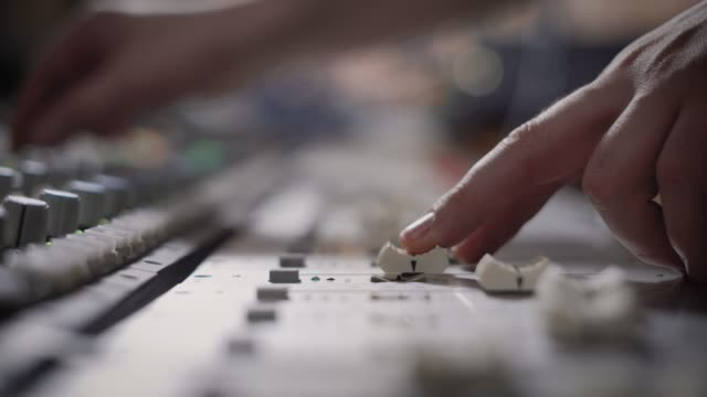 close up shot of the professional musician hands, people create music on the mixer with the help of the movement of the sliders responsible for the melody video