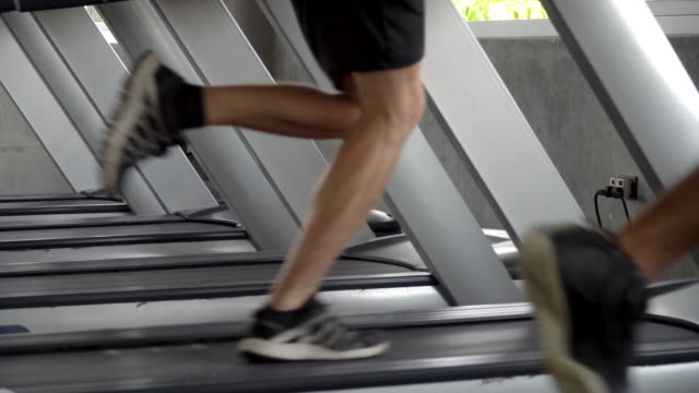4k close up shot of two athletic man legs in sport clothing running on treadmill in gym. sportsman do jogging workout training with sport equipment machine in fitness club. strong healthy lifestyle concept. - runner rehab gym video stock e b–roll