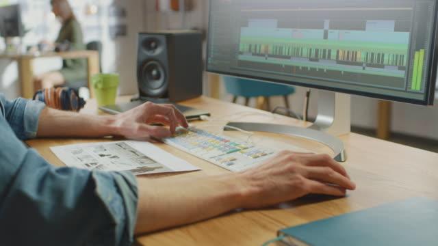 ビデオ編集者の手のクローズアップショットは、大きなディスプレイで彼のパーソナルコンピュータ上の映像を操作します。彼はクールオフィスロフトで働いています。ノートパソコンとヘ� - 編集者点の映像素材/bロール