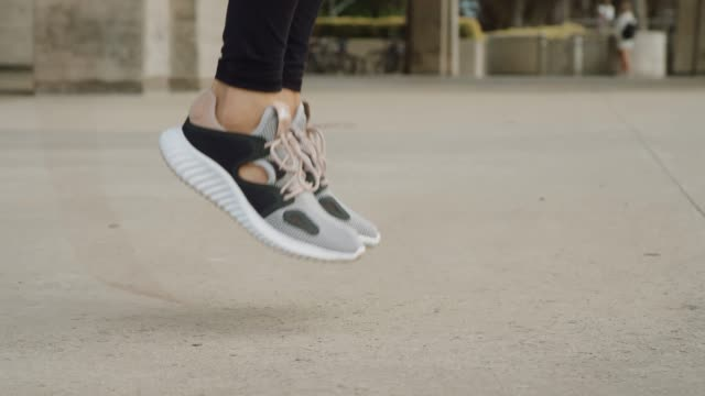 Close up shot of woman's feet jumping rope outside Slow motion shot of beautiful happy in shape athletic woman jumping rope shot in 4k cross training stock videos & royalty-free footage