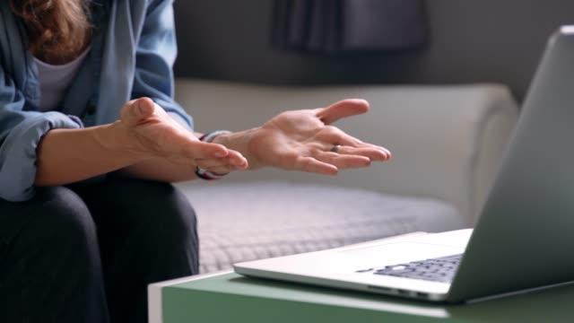 nahaufnahme der hand der frau gestikulierend vor dem laptop. - webinar stock-videos und b-roll-filmmaterial