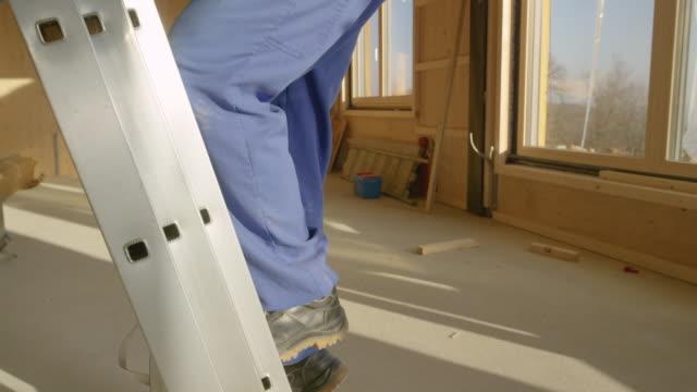 stockvideo's en b-roll-footage met close up: close-up schot van de benen van de arbeider als hij klimt een aluminium ladder. - ladder