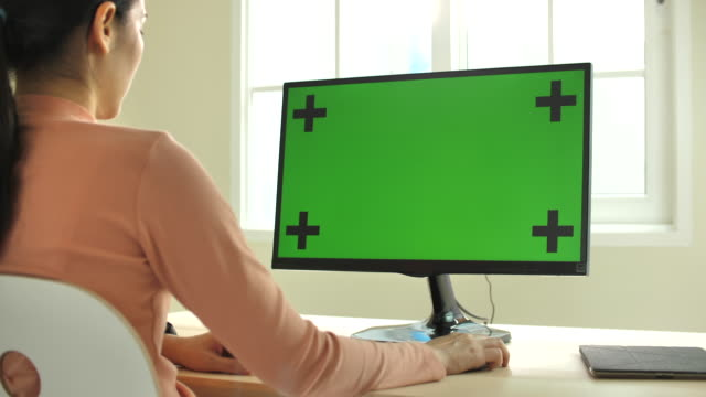 Close up shot of young Asian woman using computer with green screen at the modern Home