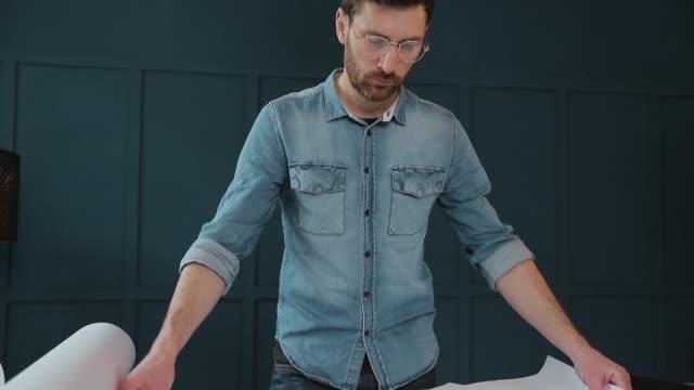 schließen sie schuss von jungen mann hände ingenieur das papier öffnen und überprüfen sie die konstruktionszeichnungen im architekturbüro. mann (hipster) stehende gesichter zum panoramafenster und blickt auf blaulicht. - pflicht stock-videos und b-roll-filmmaterial