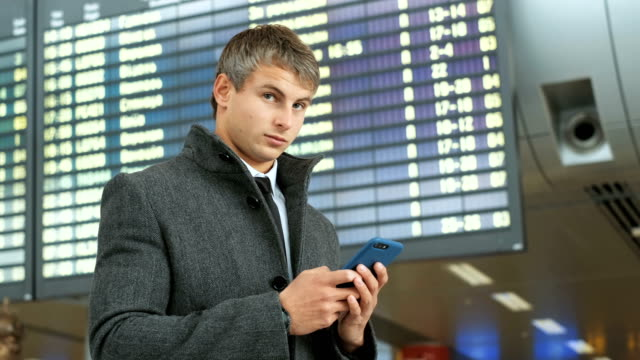 Close up shot of young man in the modern airport terminal and texting on smart phone with friends.