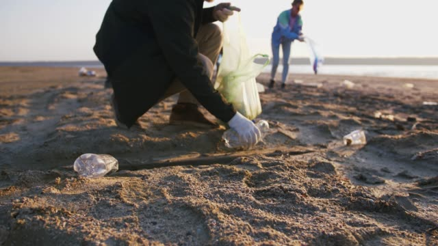 Close up shot of young man picking up plastic bottles on the beach, slow motion