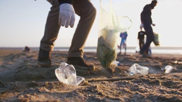 vidéos et rushes de gros plan de projectile de jeune homme ramassant des bouteilles en plastique sur la plage, ralenti - en plastique
