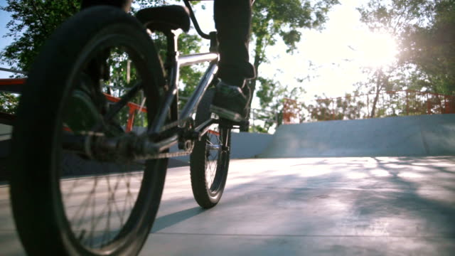 Close up shot of young man riding BMX bike in extreme park and doing tricks video