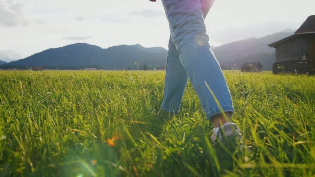 close up shot of young woman walking in beautiful green valley with mountains background, slow motion - alto video stock e b–roll