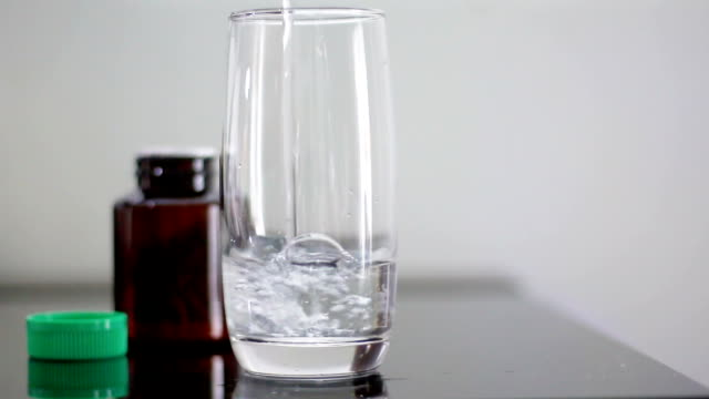 Close up shot pouring the water into clearly glass for eat the drug video