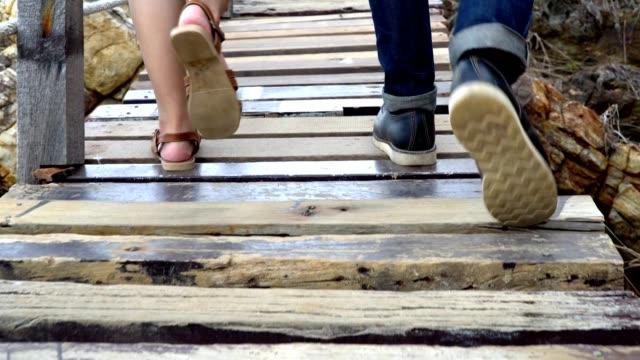 4k pov närbild skott bakifrån av par män och kvinnor reser turist ben gå på trä däck bron gångväg på klippiga havet kusten i tropiska ön berg i sommarlov semester resa. - gå tillsammans bildbanksvideor och videomaterial från bakom kulisserna