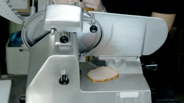 Close up shot slice machine cuts ham and meat - vídeo