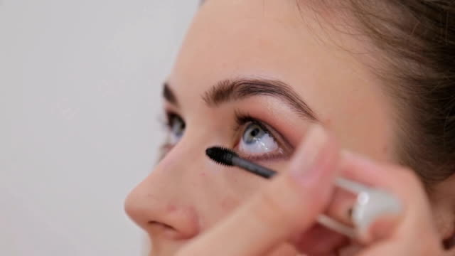 Close up shot.Professional make-up artist applying mascara on eyelashes of model video
