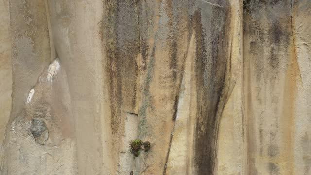 stockvideo's en b-roll-footage met sluit omhoog die de abstracte patronen in bruin en grijs van de rotsmuur van een grote klip toont - geologie