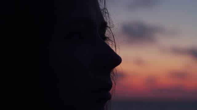 stockvideo's en b-roll-footage met close-up zijaanzicht van vrouwelijke gezicht afgetekend door zonsondergang avondlicht - portrait background