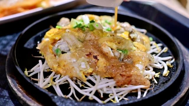 vídeos y material grabado en eventos de stock de cierre imágenes en cámara lenta de comida tailandesa o comida callejera en un plato caliente servido en el restaurante. ostra frita con harina y brotes de frijol servido en placa caliente. - comida china