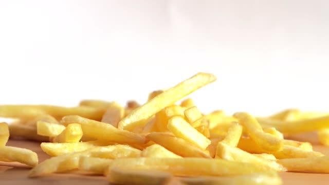 närbild slowmotion stekt potatis chips faller ner från toppen på träbord - fransk kultur bildbanksvideor och videomaterial från bakom kulisserna