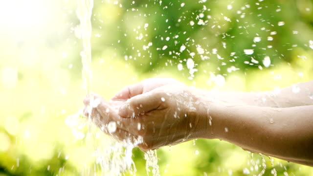 primo piano al rallentatore di acqua dolce che scorre fino alla mano di palma di un uomo con natura verde per risparmiare acqua e concetto di giornata mondiale dell'acqua - acqua dolce video stock e b–roll