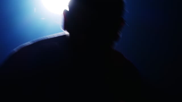 Close up slow motion of Silhouette of man doing boxing guard move with light behind him. Caucasian male.