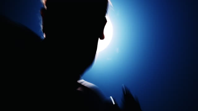 vídeos de stock, filmes e b-roll de feche a câmera lenta da silhueta do homem fazendo sombra muay thai mover-se com luz atrás dele, de frente para a câmera com efeito de neblina e vazamento de luz. homem caucasiano. - autodefesa