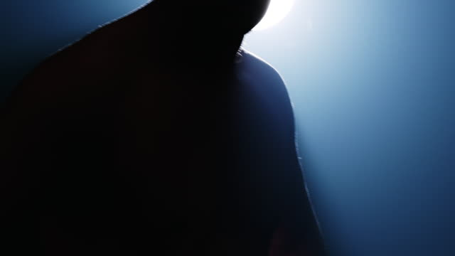Close up slow motion of Silhouette of man ready for fight, facing camera with fog and light leak effect. Caucasian male.