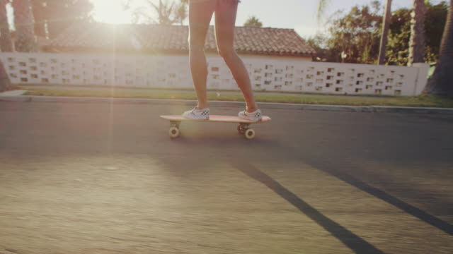 Close up slow motion shot of girls feet riding skateboard at sunset with lens flare 4k lifestyle clip of happy attractive surfer girl lifestyle on California beach shot on RED camera skating stock videos & royalty-free footage