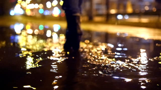 Close up slow motion shot of womans legs stepping into muddy puddle and making splash video
