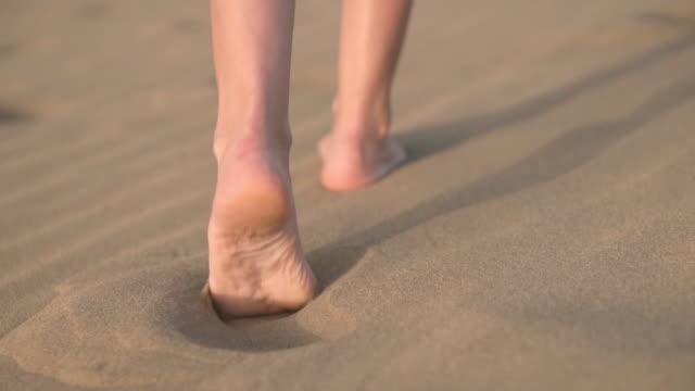 vídeos de stock, filmes e b-roll de feche, slow motion. feets da mulher que andam na areia dourada na praia. - areia