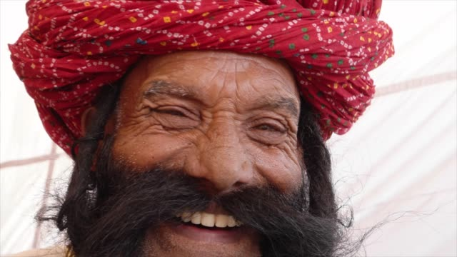 Close up Smiling man from Rajasthan salutes with big moustache wearing a red turban and tradition dress