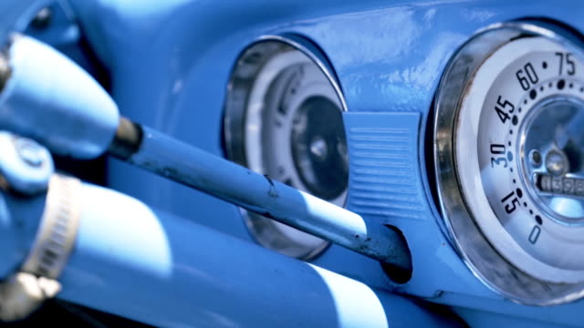 Close up Speedometer, dashboard. Action. Dashboard of a blue vintage American car