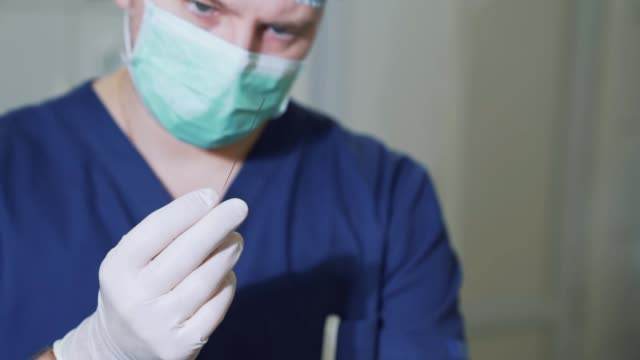 close up surgeon demonstrates a large metal needle. the doctor examines medical equipment in sterile gloves. needle for shunting of varicose veins - lama oggetto creato dall'uomo video stock e b–roll