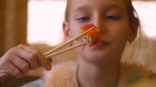 vídeos y material grabado en eventos de stock de chica adolescente comer japonés sushi roll con palillos en el restaurante asiático de cerca - sushi