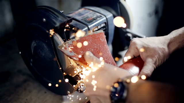 Close up the hands of a blacksmith sharpening axe on electrical grinder beautiful sparks video