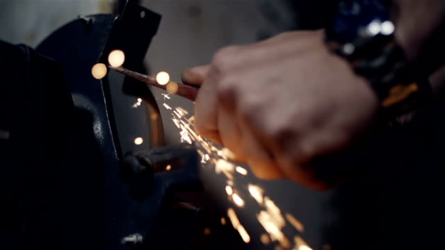 Close up the hands of a sharpening  axe on an electrical grinder beautiful sparks video