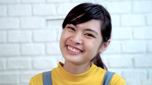 かわいい東南アジアのティーンエイジャーのビデオ撮影をクローズアップ明るくかわいい笑顔 - スタジオ 日本人点の映像素材/bロール
