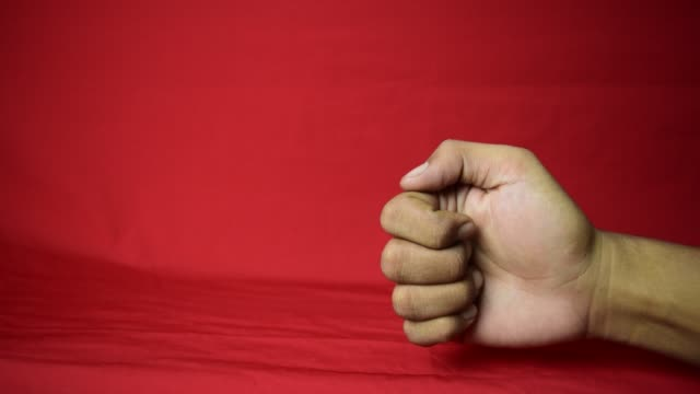 close up thumb up, ok, good sign man's hand closeup isolated at red background. - znak ok filmów i materiałów b-roll