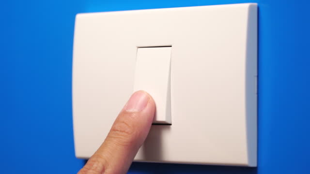 Close up to Turning off light bulb switch 4k real time of People turning off light bulb switch on blue wall background with copy space. save energy and global warming concept electric light stock videos & royalty-free footage