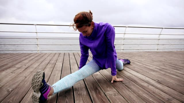 Close up view: Athletic woman stretching her legs before a jog on the beach by the sea early in the morning. Young girl doing splits. Training by the beach in summer video