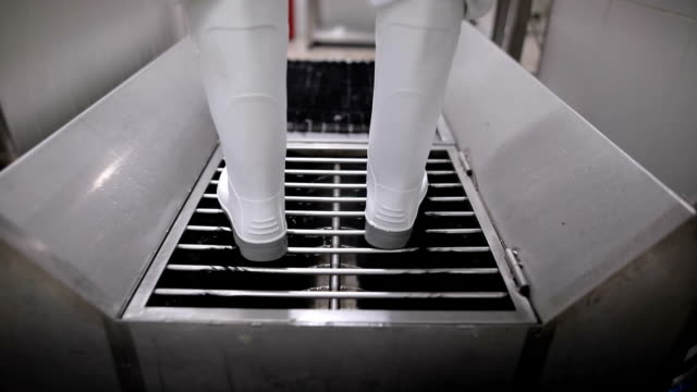 Close up view of a worker in sterile cloths washing boots before working. Hygiene at food factory