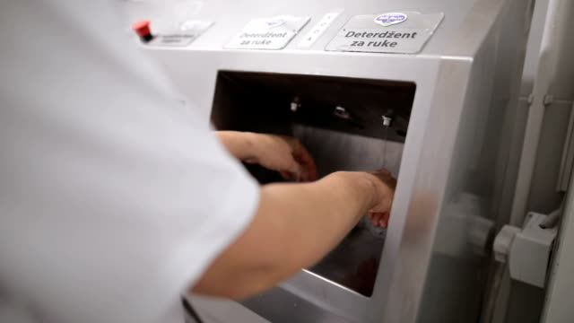 Close up view of a worker in sterile cloths washing hands before working.Hand hygiene at food factory