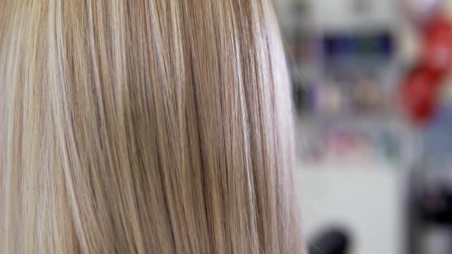 ブロンドの髪のクローズアップビュー。美容院で若い美少女。 - ブラシ点の映像素材/bロール
