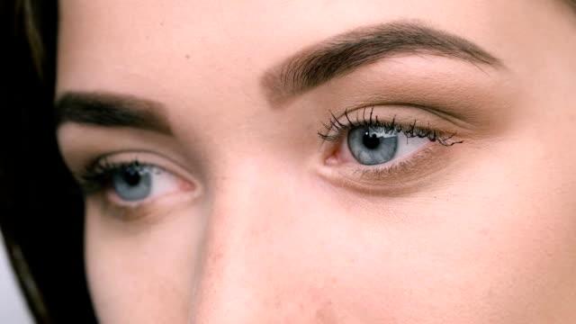 vídeos de stock e filmes b-roll de close up view of blue woman eyes with beautiful golden shades - sobrancelha