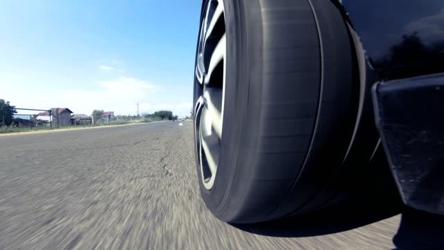 närbild på bilens hjul spining snabbt när du kör på en motorväg - wheel black background bildbanksvideor och videomaterial från bakom kulisserna