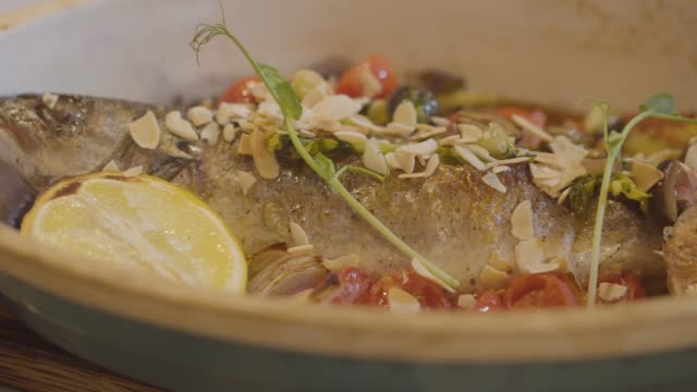 Close up view of fresh baked fish lying in deep plate