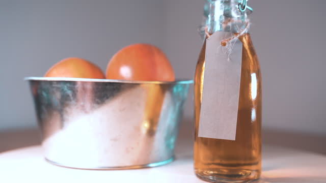 Close up view of glass bottle of apple juice and apples in basket on wooden tabletop