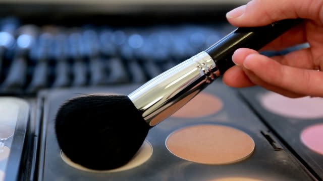 Close up view of makeup brush moving over skin and eyeshadow color palette video