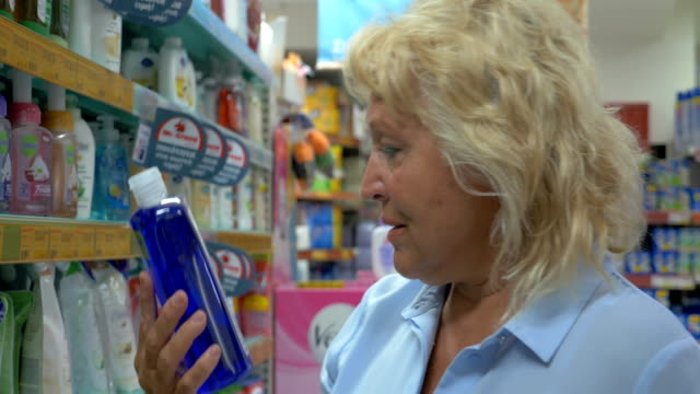Close up view of senior woman is choosing cleanser in a bottle at supermarket and reading package for cleaning Close up view of senior blond woman in blue blouse is watching dish soap at supermarkets aisle and researching consist package dishwashing liquid stock videos & royalty-free footage