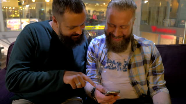 Close up view of two white mature bearded men using smartphone together video