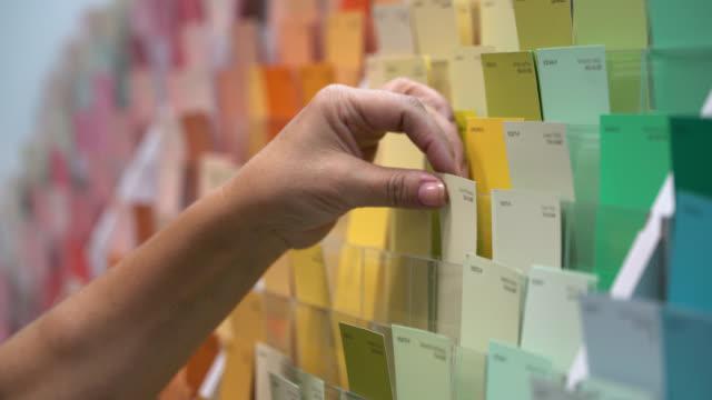vídeos y material grabado en eventos de stock de vista de cerca de un cliente femenino irreconocible eligiendo una muestra de color en un taller de pintura - escoger